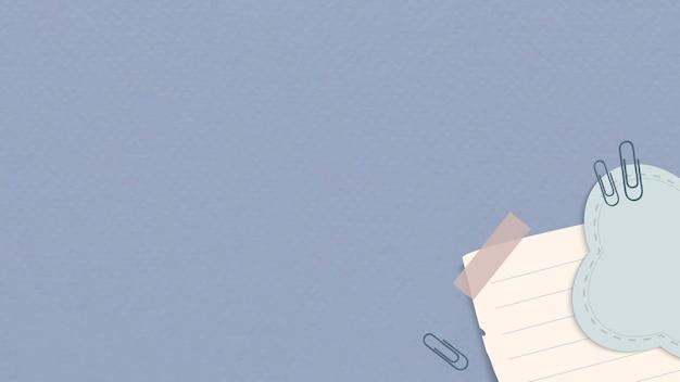 Papel de carta de decoración de esquina con clips y cinta sobre fondo azul.