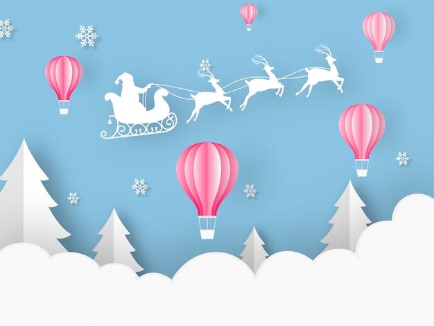 Papel cortado estilo globos de aire caliente, árbol de navidad, copos de nieve y silueta santa montando trineo de renos sobre fondo azul nublado para la celebración de feliz navidad.