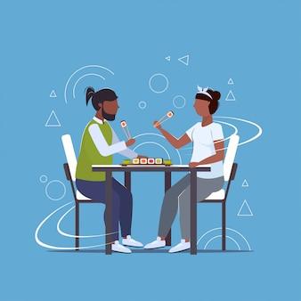 Par comer sushi estilo de vida poco saludable concepto sobrepeso hombre mujer sentada en la mesa disfrutando de comida rápida plana de cuerpo entero