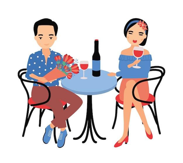 Par de hombre y mujer jóvenes sentados a la mesa y bebiendo vino tinto juntos