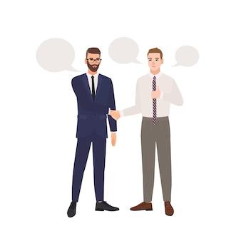 Par de hombres de negocios vestidos con trajes de negocios de pie, hablando entre sí y dándose la mano.