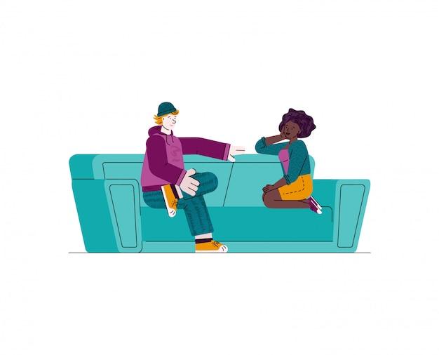 Pareja adolescente sentado en el sofá verde y hablando - hombre y mujer joven