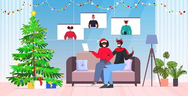Pareja afroamericana en máscaras discutiendo con amigos durante la videollamada concepto de cuarentena de coronavirus año nuevo vacaciones de navidad celebración interior de la sala de estar de cuerpo entero enfermo