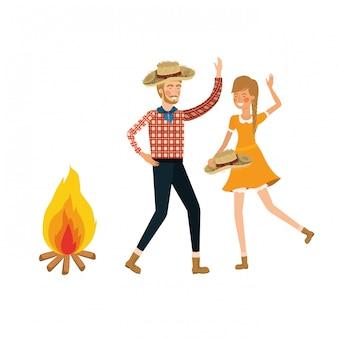Pareja de agricultores bailando con sombrero de paja y hoguera