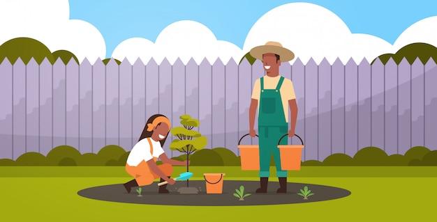 Pareja de agricultores plantando árbol joven hombre sosteniendo cubos de agua mujer cavando el suelo trabajando en el jardín concepto de jardinería agrícola fondo patio horizontal de longitud completa