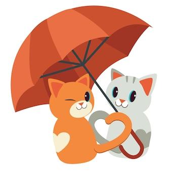 La pareja ama a los gatos. se sentaron bajo el paraguas rojo. el gato y la sombrilla. la cola se parece al corazón. los gatos se ven felices.