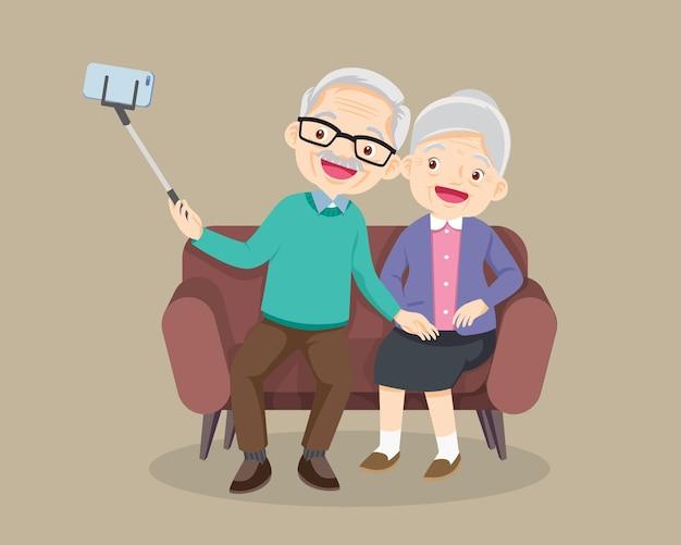 Pareja de ancianos sentados en el sofá y haciendo fotos juntos en el teléfono móvil con selfie stick