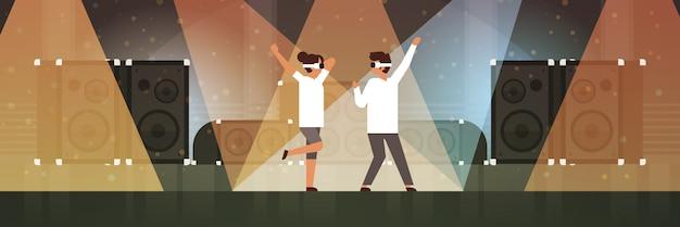 Pareja de bailarines con gafas de realidad virtual bailando en el escenario con efectos de luz discoteca estudio equipo musical altavoz multimedia