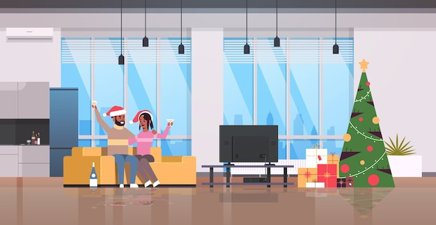 Pareja bebiendo champán feliz navidad feliz año nuevo celebración navideña víspera concepto de fiesta hombre mujer con gorro de papá noel sentado en el sofá moderno salón interior ilustración vectorial horizontal de longitud completa