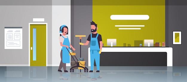 Pareja conserjes hombre mujer en uniforme trabajando juntos servicio de limpieza limpiadores empujando carrito con herramientas moderno hospital recepción interior
