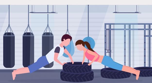Pareja deportiva haciendo ejercicio de flexiones sobre neumáticos hombre mujer trabajando juntos entrenamiento crossfit concepto de estilo de vida saludable gimnasio moderno interior plano horizontal