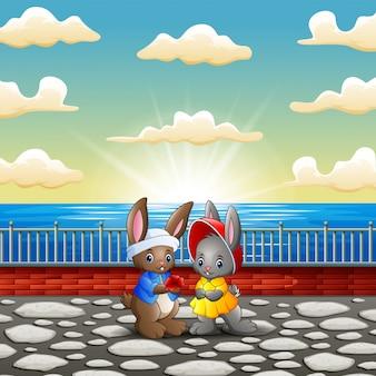Pareja de dibujos animados de conejo en la orilla del río con puesta de sol