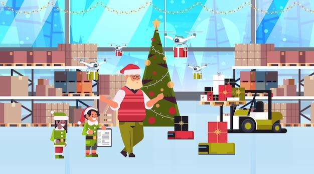 Pareja de elfos ayudantes de santa claus trabajando juntos con cajas de regalo presentes en el interior del almacén moderno concepto de celebración de vacaciones de navidad