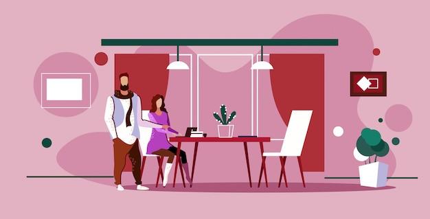 Pareja de empresarios de intercambio de ideas empresaria con asistente masculino usando laptop discutiendo nuevo proyecto durante la reunión en el lugar de trabajo moderno interior de la oficina