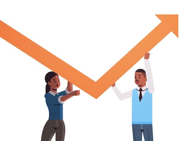 Pareja de empresarios sosteniendo flecha hacia arriba trabajo en equipo concepto de crecimiento financiero empresarios afroamericanos corrigiendo la dirección del retrato horizontal gráfico