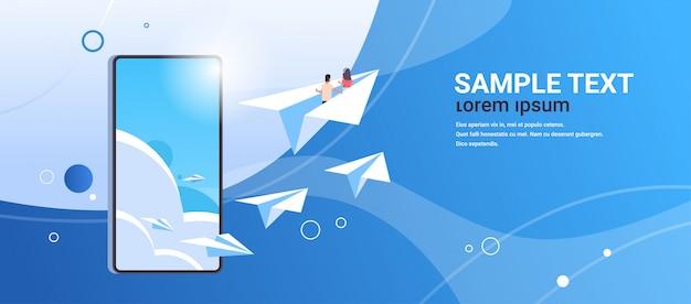 Pareja de enamorados volando en avión de papel hombre mujer amantes viajando juntos concepto romántico pantalla del teléfono inteligente aplicación móvil en línea