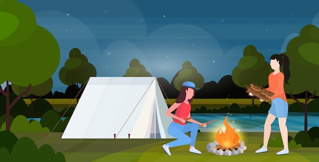 Pareja de excursionistas haciendo fuego chicas sosteniendo leña para hoguera senderismo concepto mujeres viajeras en caminata tienda de campaña camping naturaleza paisaje fondo horizontal de longitud completa plana