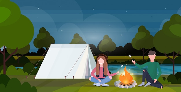 Pareja excursionistas tostar caramelos de malvavisco en fogata senderismo concepto camping hombre mujeres viajeros en caminata paisaje nocturno naturaleza fondo horizontal de longitud completa plana