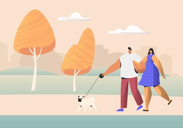 Pareja familiar de personajes jóvenes caminando con mascota en el parque público de la ciudad en verano.