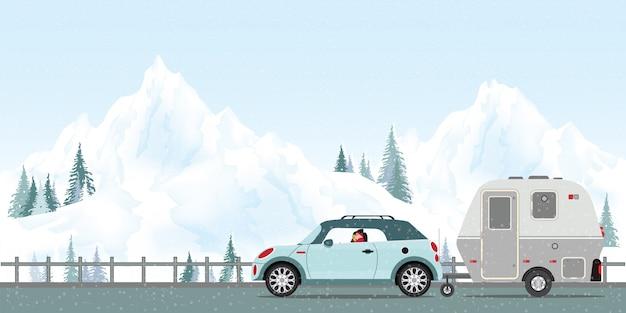 Pareja feliz conduciendo el coche en carretera en invierno.