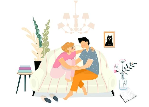 Pareja joven abrazo escena de amor sentado en el sofá o sofá y abrazándose. la gente cotidiana vive, novia y novio noche romántica en casa.