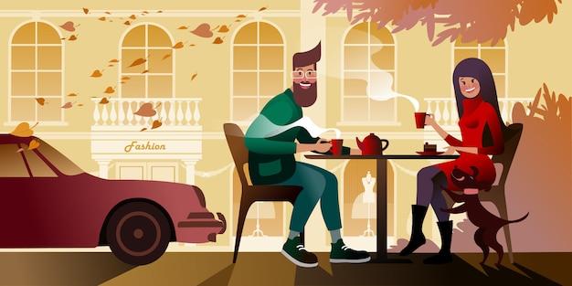 Pareja joven bebiendo té en la terraza de otoño del café de la ciudad. escena callejera de la ciudad.