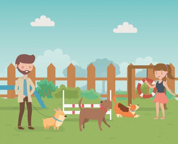 Pareja joven con lindas perritos mascotas en el campo