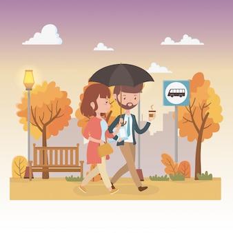 Pareja joven con paraguas caminando en los personajes del parque