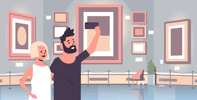 Pareja joven tomando foto selfie en teléfono inteligente cámara hombre mujer visitantes en la galería de arte moderno museo interior retrato horizontal
