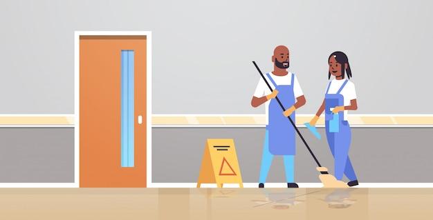 Pareja de limpiadores en uniforme trabajando juntos concepto de servicio de limpieza hombre mujer conserjes usando mop spray botella de plástico moderno clínica pasillo interior longitud completa