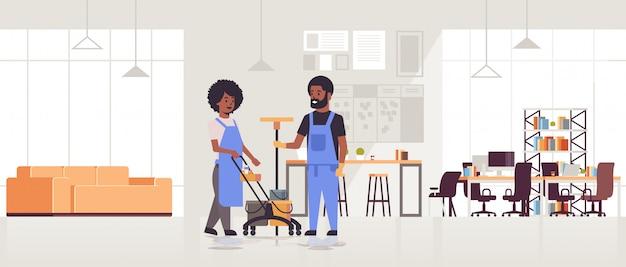 Pareja de limpiadores en uniforme trabajando juntos limpiadores de concepto de servicio de limpieza utilizando carro de carro con herramientas moderno centro de trabajo interior de la oficina horizontal de longitud completa
