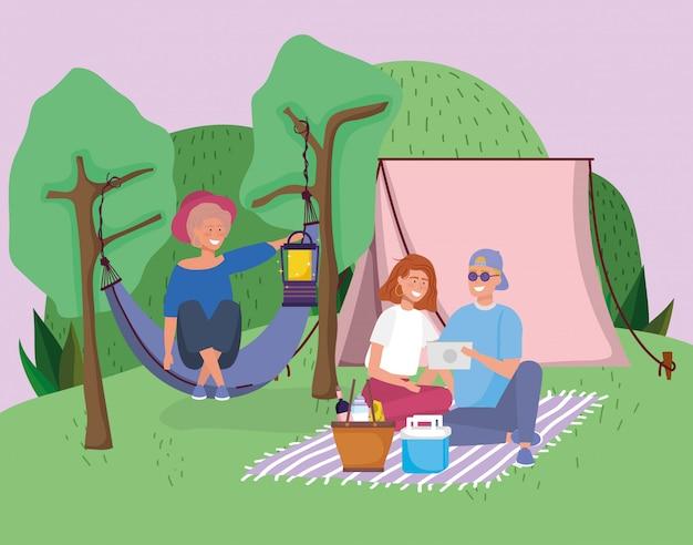 Pareja con manta tableta y mujer en hamaca carpa camping picnic
