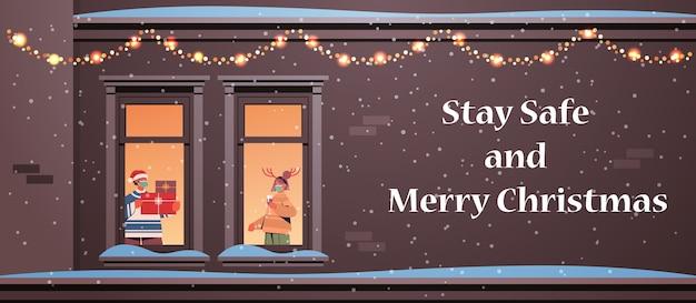 Pareja en máscaras sosteniendo regalos hombre mujer de pie en marcos de ventana año nuevo vacaciones de navidad celebración concepto de autoaislamiento edificio fachada de casa ilustración vectorial horizontal