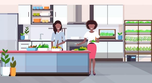 Pareja de mujeres que preparan la ensalada de verduras concepto de comida saludable sala de casa moderna con plantas inteligentes sistema de cultivo interior de la cocina plana horizontal de longitud completa