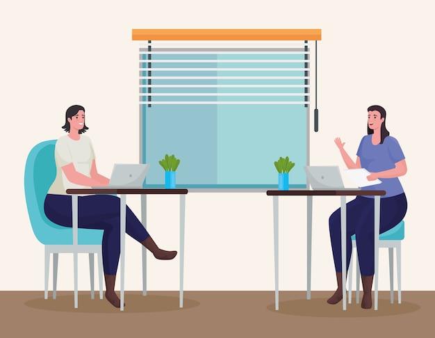 Pareja de mujeres que usan computadoras portátiles para reunirse en línea en el lugar de trabajo