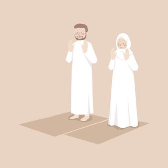 Pareja musulmana levanta las manos para hacer takbirat al ihram en oración, orando juntos en posición en la alfombra de oración
