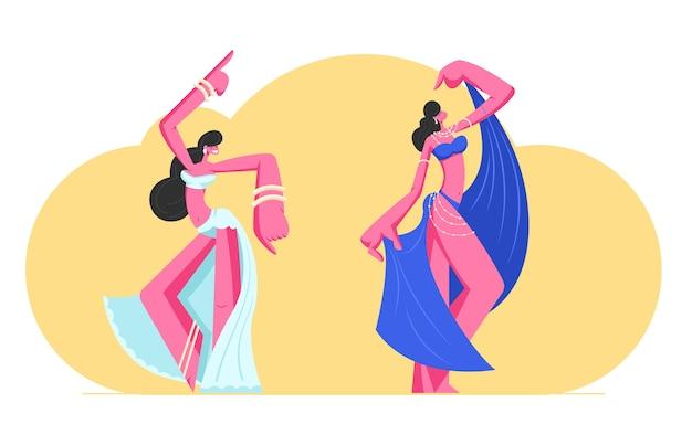 Pareja de niñas en hermosos vestidos árabes y joyas bailando danza del vientre con manos levantadas