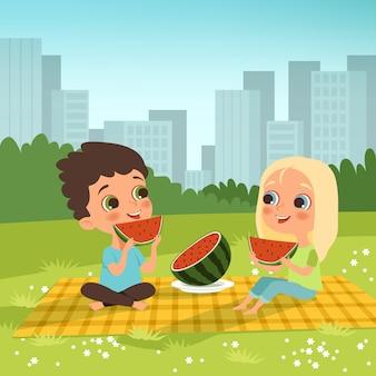 Pareja de niños sentados en el jardín urbano y comer algunas frutas.