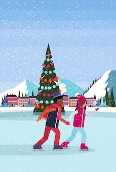 Pareja patinando en la pista de hielo con un árbol de navidad decorado en el hotel resort de esquí