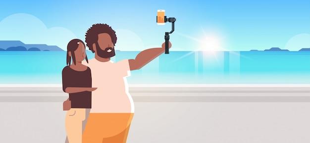 Pareja de pie juntos mar playa hombre mujer sosteniendo selfie palo tomando fotos en el teléfono inteligente