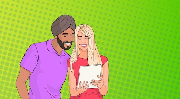 Pareja de raza mixta que usa la computadora de la tableta que chatea en línea sobre el fondo de estilo retro colorido del arte pop