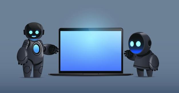 Pareja de robots modernos de pie cerca de la computadora portátil con tecnología de inteligencia artificial de carácter robótico de pantalla en blanco