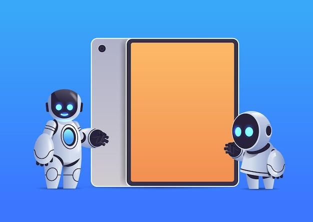 Pareja de robots modernos de pie cerca de la tableta con tecnología de inteligencia artificial de carácter robótico de pantalla en blanco