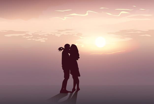Pareja romántica silueta abrazar al atardecer amantes beso de hombre y mujer