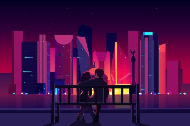 Pareja sentada en el banco en el terraplén de la ciudad, hombre y mujer disfrutando de la vista nocturna de la ciudad