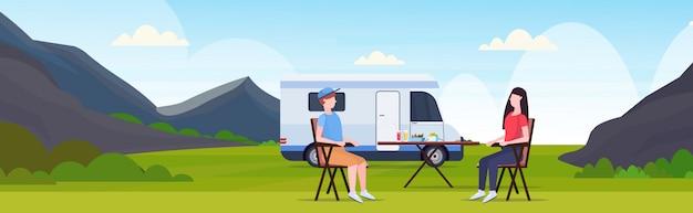 Pareja sentada en la mesa cerca de camping familia remolque camión caravana coche hombre mujer pasar tiempo juntos concepto de vacaciones de verano precioso naturaleza paisaje fondo plano de longitud completa horizontal