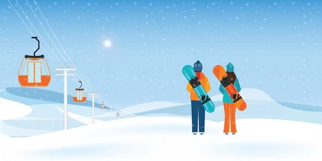 Pareja de snowboarders de pie con tablas de snowboard.