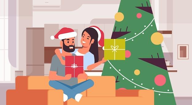 Pareja sosteniendo cajas de regalo feliz navidad feliz año nuevo celebración de vacaciones concepto hombre mujer abrazando vistiendo gorro de papá noel sentado en el sofá cerca del árbol en forma moderna sala de estar interior vector horizontal