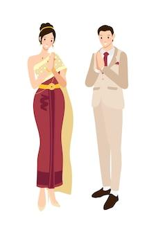 Pareja tailandesa de bodas que saluda con traje y vestido oscuros azul grisáceo tradicionales