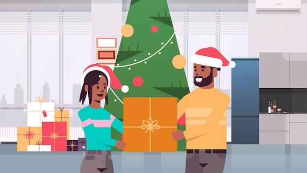 Pareja, tenencia, regalo, caja presente, feliz navidad, feliz año nuevo, celebración navideña, concepto, hombre mujer, llevando, santa, sombreros, posición, cerca, ajuste, árbol, moderno, sala, interior, horizontal, retrato, vector